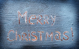 Words Merry Christmas on snowy desk. Royalty Free Stock Image