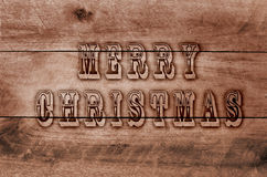 Words Merry Christmas written, burned letters on wooden brown background Stock Image