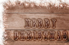 Words Merry Christmas written, burned letters on wooden snowy brown background Royalty Free Stock Image