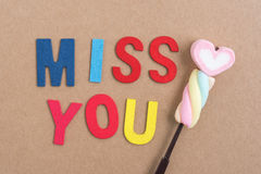 Words miss you with heart candy. On brown background Royalty Free Stock Photo
