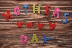 Words MOTHER'S DAY composed of glitter letters on wooden background. Mother's Day royalty free stock photo