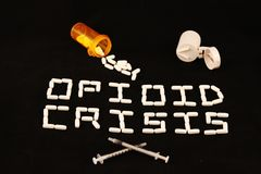 Opioid crisis spelled out with white pills on a black background with spilled prescription pills and a pill cutter. Royalty Free Stock Photography