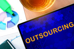 Words Outsourcing  on the tablet and charts. Royalty Free Stock Photography