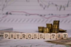 Words PAYROLL TAX composed of wooden letter. Stacks of coins in the background. Closeup stock photography
