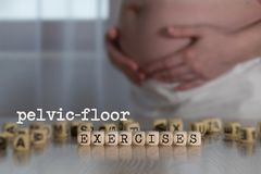 Words PELVIC-FLOOR EXERCISES composed of wooden letters. Pregnant woman in the background royalty free stock image