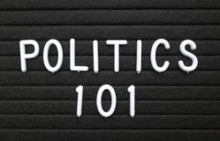The words Politics 101 in white text on a letter board. The words Politics 101 in white plastic letters on a black letter board as an introduction to the basics stock image