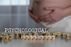 Words PSYCHOLOGICAL IMBALANCE composed of wooden letters. Pregnant woman in the background stock photography