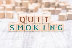 The Words Quit Smoking Formed By Wooden Blocks On A White Table, Reminder Concept royalty free stock photo