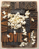 Words related to movies with popcorn. Words associated with movie watching in old letterpress wood and metal type with popcorn stock photos