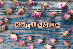 Reliable on wooden cube. The words reliable write on wooden cubes with rose bud on blue color wood background stock photo