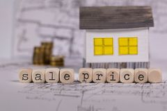 Words SALE PRICE composed of wooden letter. Small paper house in the background. Closeup stock image