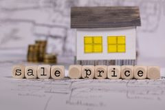 Words SALE PRICE composed of wooden letter. Small paper house in the background. Closeup royalty free stock images