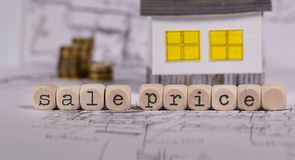 Words SALE PRICE composed of wooden letter. Small paper house in the background. Closeup royalty free stock photo