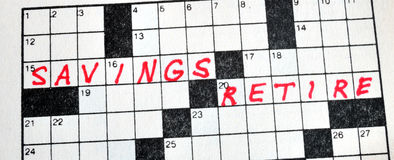 The Words Savings and Retire on Crossword Puzzle. In Red Ink, Copy Space Stock Image