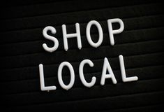 The words Shop Local on a Notice Board. The words Shop Local in white plastic letters on a notice board stock photos