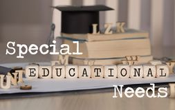 Words SPECIAL EDUCATIONAL NEEDS composed of wooden dices. Black graduate hat and books in the background. Closeup stock images