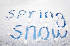 Words of SPRING SNOW written in the snow on a blue car Royalty Free Stock Photography