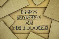 Words Stay Strong Be Different make by black alphabet stamps on. Cardboard with some piece of cardboard Royalty Free Stock Image