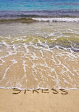 Words Stress written on sand, washed away by waves. Relax concept stock images