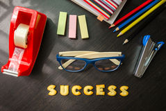 The words: success made of cookies. The words: success made of cookies, glasses and stationeries on black table Royalty Free Stock Image
