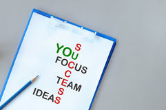 Words of success, team, ideas and focus and you on notepad. On grey background business concept and success idea Stock Photo