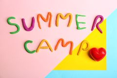 Words SUMMER CAMP made from modelling clay. And small red heart on color background, top view Stock Photography