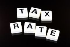 The Words Tax Rate - A Term Used For Business in Finance and Stock Market Trading. The Words Tax Rate Spelled Out With White Tiles On Black Background Stock Photos