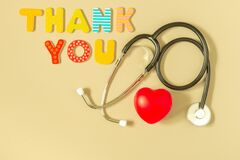 Words THANK YOU, stethoscope and red heart on yellow background