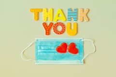 Words THANK YOU of wooden letters and face protection mask