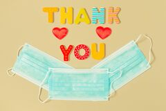 Words THANK YOU of wooden letters and face protection masks in smile shape