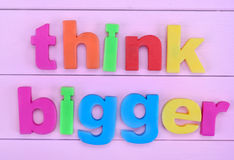 Words Think Bigger on pink table Stock Image