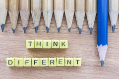 Words Think Different on wooden table with group of pencils Stock Image