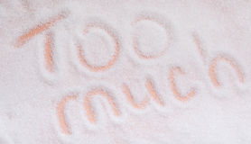 The words too much written in sugar grains. Overhead view. royalty free stock photography