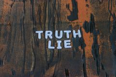 The words truth and lie written in white block letters. On a orange and brown wood surface Stock Photography