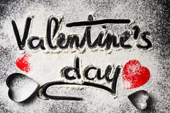 Words Valentines Day, written in flour and decorations from paper red hearts on a dark background. Valentine`s Day concept stock photography