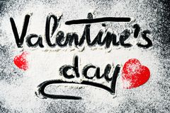 Words Valentines Day, written in flour and decorations from paper red hearts on a dark background. Valentine`s Day concept royalty free stock images