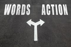 Words vs action  choice concept. Two direction arrows on asphalt Royalty Free Stock Photography