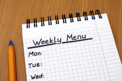 Words Weekly Menu written on white note pad with pen Royalty Free Stock Photography