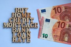 Words on a white background lined in the form of a house of wooden letters next to two bills of 10 euros. The concept of buying re stock photo