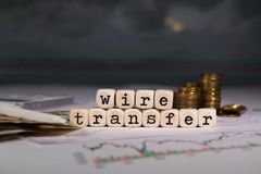 Words WIRE TRANSFER composed of wooden letter. Stacks of coins in the background. Closeup stock image