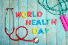 """Words \""""World Health Day\"""" made with letters and medical stethoscope on wooden background"""