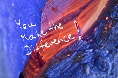 Words You make the difference! handwritten on red burn wooden background Royalty Free Stock Photography