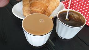 Wordt de koffie hete melk gegoten in kop van croissant stock videobeelden