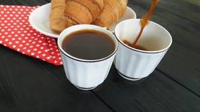 Wordt de koffie hete melk gegoten in kop van ontbijtcroissant stock videobeelden