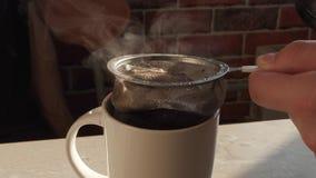 Wordt de vers gebrouwen hete op smaak gebrachte koffie gegoten in een kop en door een zeef gefiltreerd stock footage