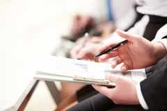 During work. Business person hand with pen learning document during lecture Stock Photography