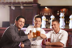 After work. Young business men in a bar with beer Stock Photo