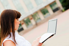 At work. Business woman working on the street with a netbook Stock Photography