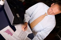 At work. Young businessman at work covered with papers stock photography