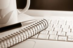 Work. A mug, a pen, and a notebook on a laptop keyboard. Shallow depth of field. Focus around the area of the pen tip Stock Images